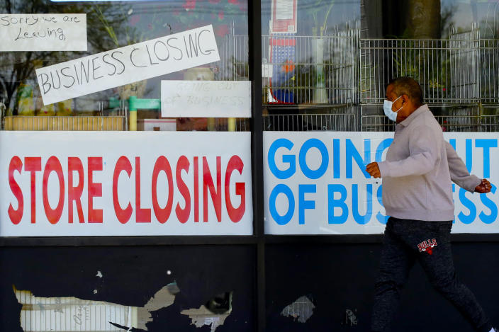 A man looks at signs of a closed store due to COVID-19 in Niles, Ill., Thursday, May 21, 2020. (AP Photo/Nam Y. Huh)