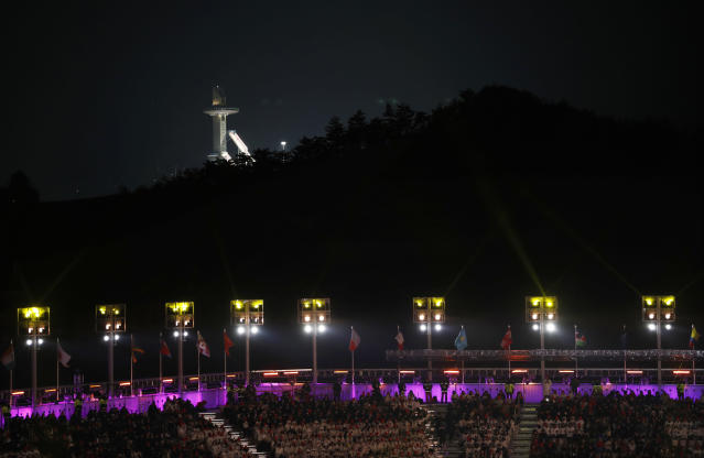 The Alpensia Ski Jumping Center towers are illuminated in the background while people attend the closing ceremony of the 2018 Winter Olympics in Pyeongchang, South Korea, Sunday, Feb. 25, 2018. (AP Photo/Charlie Riedel)