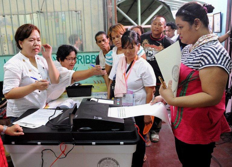 A woman (R) scans a ballot on an electronic vote-counter at a polling station during mid-term elections in Manila, on May 13, 3013. People are going to the polls to choose thousands of local leaders plus national legislators in what is seen as a referendum on the presidency of reformist Benigno Aquino