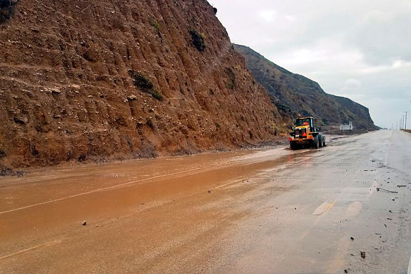 This photo provided by the California Department of Transportation (CalTrans) shows a skiploader clearing a river of mud that has flowed onto Pacific Coast Highway in Malibu, Calif., Jan. 14, 2019. The first in a series of Pacific storms is moving across Southern California, where downpours could unleash mud and debris flows from large wildfire burn scars.