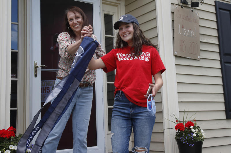 In this June 1, 2020 photo, high school graduate Lizzie Quinlivan and her mom, Julie, hold a Georgetown University windsock at their home in Hingham, Mass. Quinlivan has opted to attend closer-to-home Georgetown instead of colleges on the west coast which were on her original wish-list.  As students make college plans for this fall, some U.S. universities are seeing surging interest from in-state students looking to stay closer to home amid the coronavirus pandemic. (AP Photo/Elise Amendola)