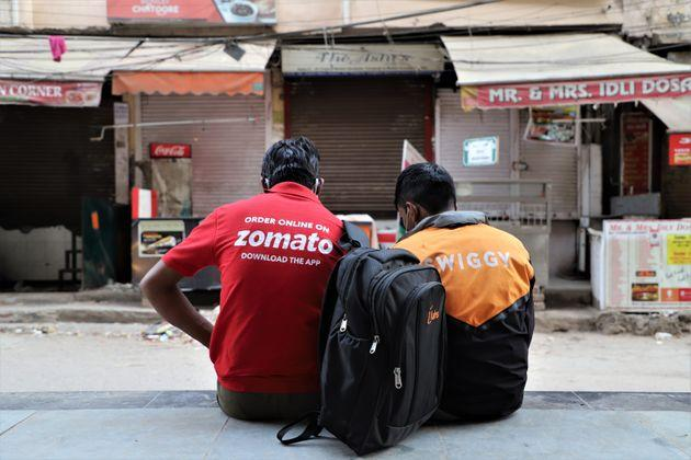 Swiggy and Zomato delivery partners rest near closed restaurants in DLF Phase III, Gurugram on the outskirts of New Delhi on 05 April 2020.