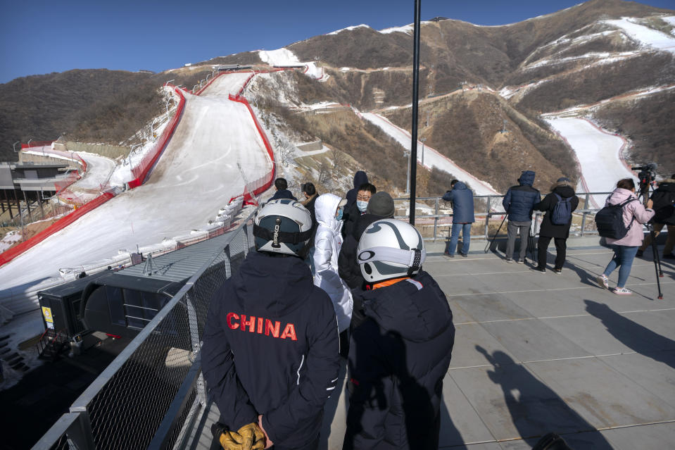 A skier wearing a China jacket stands at the National Alpine Skiing Center in Yanqing on the outskirts of Beijing, Friday, Feb. 5, 2021. Beijing Olympic organizers showed off the downhill skiing venue and the world's longest bobsled and luge track Friday, one year ahead of the scheduled opening of the 2022 Olympic Winter Games. (AP Photo/Mark Schiefelbein)