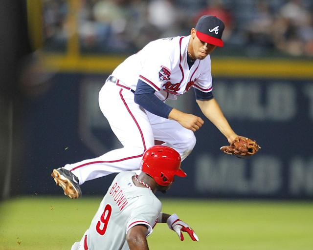 Atlanta Braves shortstop Andrelton Simmons (19) turns the double play as Philadelphia Phillies Domonic Brown (9) slides into second in the ninth inning of a baseball game Tuesday, June 17, 2014, in Atlanta. (AP Photo/Todd Kirkland)