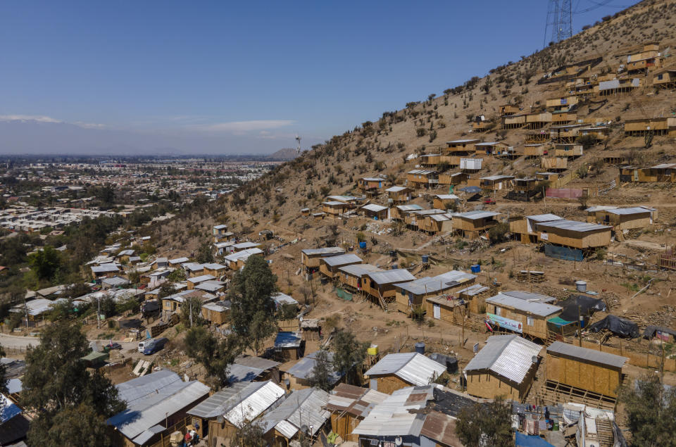 """Homes stand on the side of a hill in an unpaved area named """"Bosque Hermoso,"""" or Beautiful Forest, where migrants from Haiti, Peru and Colombian settled in Lampa, Chile, Friday, Oct. 1, 2021. The situation of the migrants became more difficult in 2018 when Chile's government issued a decree requiring that Haitians obtain a consular visa before traveling to Chile, then last April enacted a new migration law that seeks to prevent the irregular entry of foreigners. (AP Photo/Esteban Felix)"""