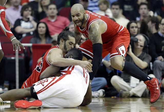 Chicago Bulls' Joakim Noah, left, and Carlos Boozer, right, try to get the ball away from Houston Rockets' James Harden (13) in the first half of an NBA basketball game on Wednesday, Dec. 18, 2013, in Houston. (AP Photo/Pat Sullivan)