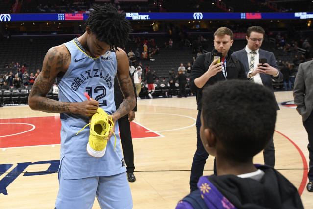 Memphis Grizzlies guard Ja Morant (12) signs his shoes to give to a fan after an NBA basketball game against the Washington Wizards, Sunday, Feb. 9, 2020, in Washington. The Grizzlies won 106-99. (AP Photo/Nick Wass)