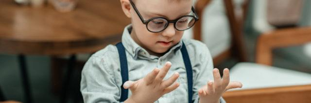A boy with Down syndrome looks at his hands,. He's wearing glasses and suspenders.