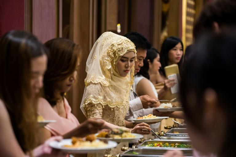 Guests choose halal food items during a wedding reception at the Al Meroz hotel in Bangkok