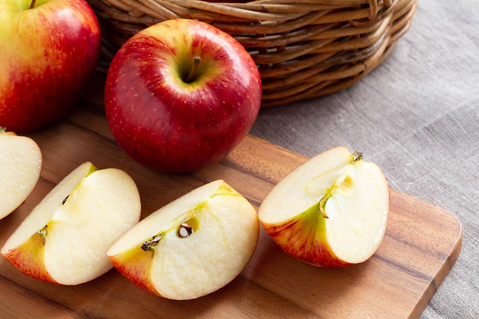 Red ripe apples and cut apples on the cutting board
