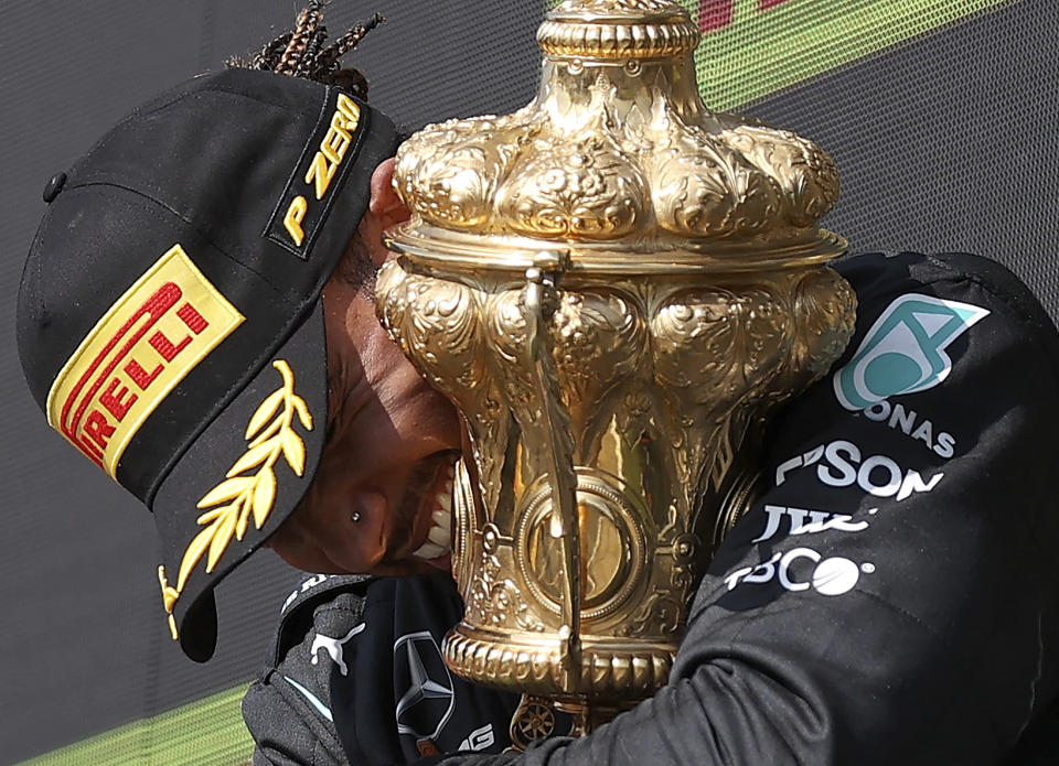 Mercedes driver Lewis Hamilton of Britain celebrates on the podium after winning the British Formula One Grand Prix, at the Silverstone circuit, in Silverstone, England, Sunday, July 18, 2021. (Lars Baron/Pool photo via AP)