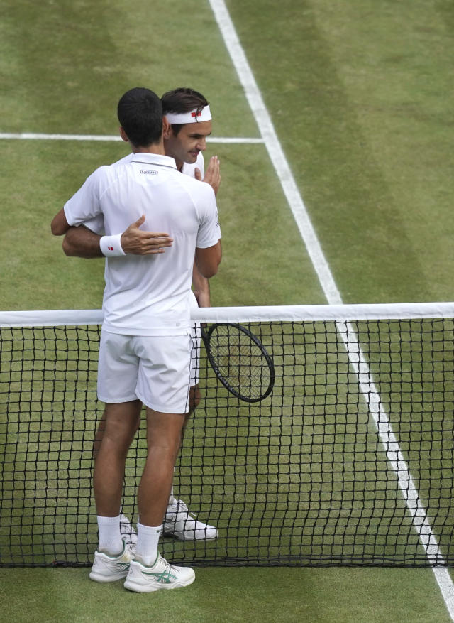 Serbia's Novak Djokovic, left, hugs Switzerland's Roger Federer after he defeats him during the men's singles final match of the Wimbledon Tennis Championships in London, Sunday, July 14, 2019. (Will Oliver/Pool Photo via AP)