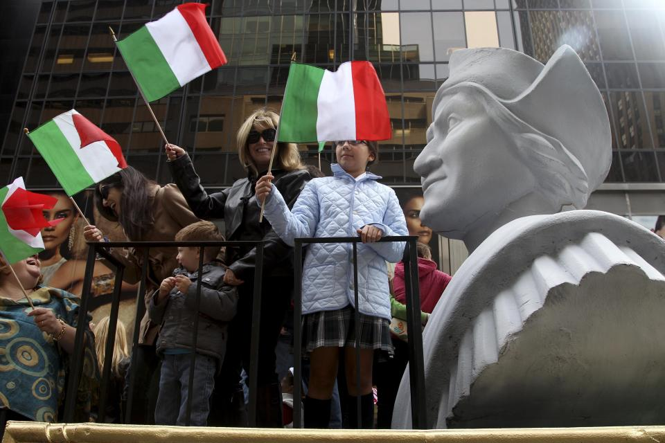 FILE - In this Oct. 8, 2012 file photo, people ride on a float with a large bust of Christopher Columbus during the Columbus Day parade in New York. Monday, Oct. 11, 2021 federal holiday dedicated to Christopher Columbus continues to divide those who view the explorer as a representative of Italian Americans' history and those horrified by an annual tribute that ignores the native people whose lives and culture were forever changed by colonialism.(AP Photo/Seth Wenig, File)
