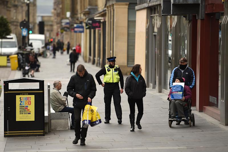 A police community support officer encourages people to socially distance in the centre of Newcastle upon Tyne, Thursday lunchtime in north-east England on April 9, 2020 as Britain continued to battle the outbreak of new coronavirus and the governement prepared to extend the nationwide lockdown. - The disease has struck at the heart of the British government, infected more than 60,000 people nationwide and killed over 7,000, with another record daily death toll of 938 reported on April 8. A testing centre opened in Gateshead on April 9, 2020 as the government ramped up its testing of NHS staff for the new coronavirus. (Photo by Oli SCARFF / AFP) (Photo by OLI SCARFF/AFP via Getty Images)