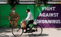 A man cycles past a graffiti covered wall amidst the spread of the coronavirus disease (COVID-19) on a street in Navi Mumbai