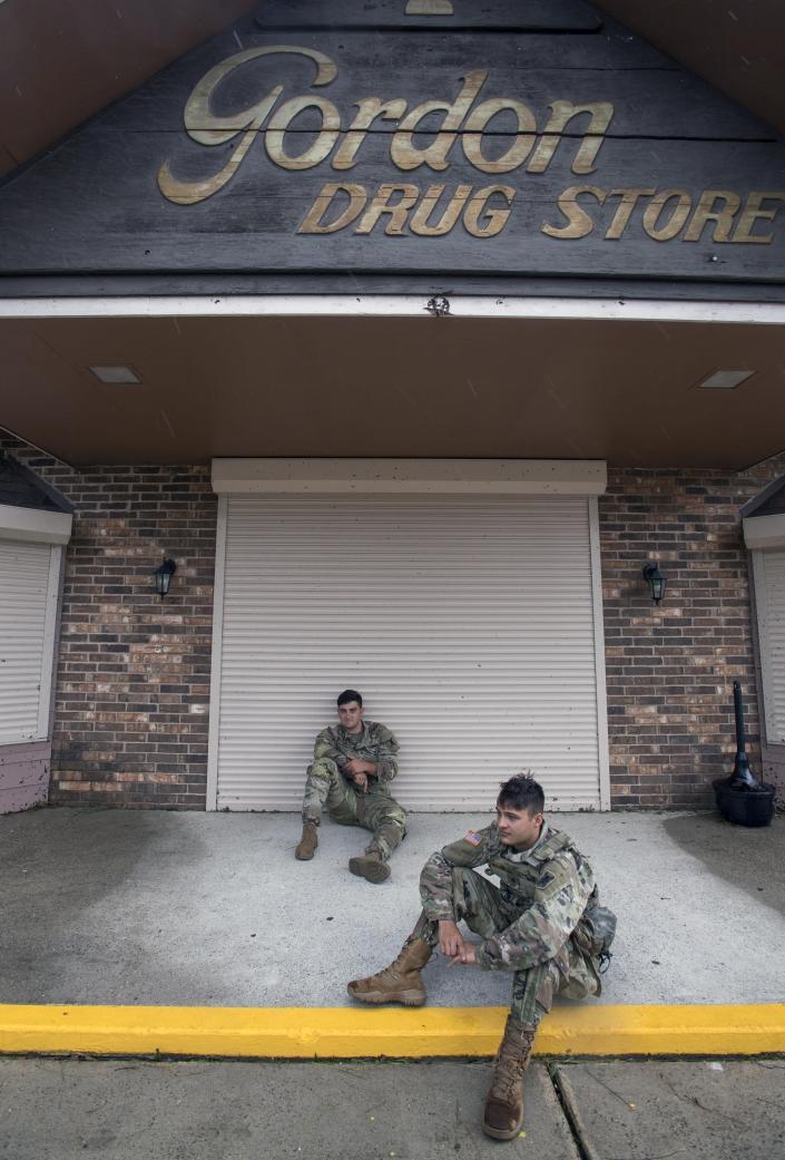 Louisiana National Guardsmen Sgt. Austin Hernandez, center, and Spc. Beau Scoggin, both of New Iberia, guard a drug store Friday, Aug. 28, 2020 in Lake Charles. Recovery efforts were underway after Hurricane Laura. (Chris Granger/The Times-Picayune/The New Orleans Advocate Via AP)