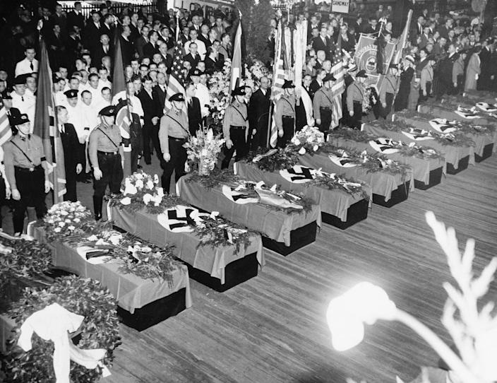 <p>Funeral services for the 28 Germans who lost their lives in the Hindenburg disaster May 6 are held on the Hamburg-American pier in New York City, May 11, 1937. The swastika-draped caskets will be placed on board the Hamburg for their return to Europe. About 10,000 members of German organizations line the pier. (AP Photo/Anthony Camerano) </p>