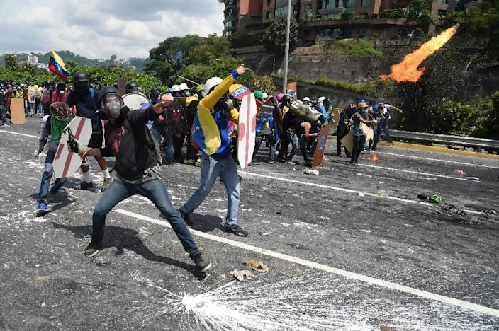 A demonstrator throws a molotov cocktail to the riot police as clashes erupt during a march against President Nicolas Maduro in Caracas, on May 10, 2017 (AFP Photo/JUAN BARRETO )