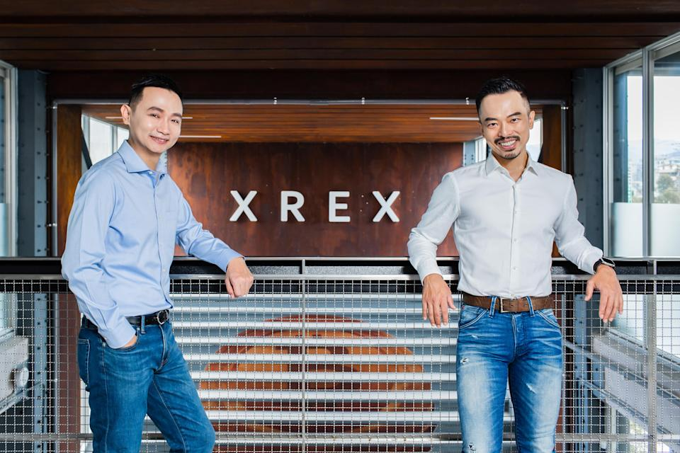 Blockchain startup co-founders Winston Hsiao and Wayne Huang in front of the company's logo