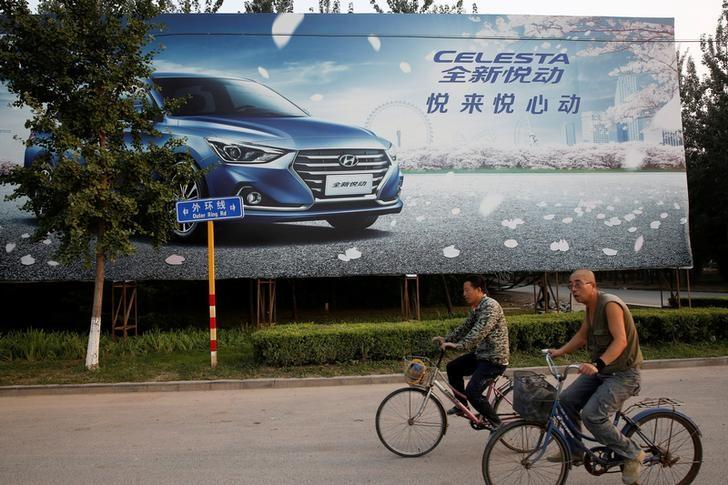 Men cylce past an advertising billboard for Hyundai cars opposite the plant of Hyundai Motor Co in Beijing, China, August 30, 2017. REUTERS/Thomas Peter/File Photo