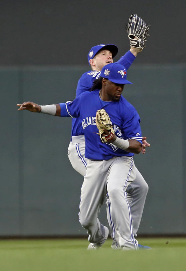 Toronto Blue Jays right fielder Billy McKinney, rear, catches a fly ball by Minnesota Twins' Mitch Garver after colliding with second baseman Alan Hanson, front, in the third inning of a baseball game Monday, April 15, 2019, in Minneapolis. (AP Photo/Jim Mone)