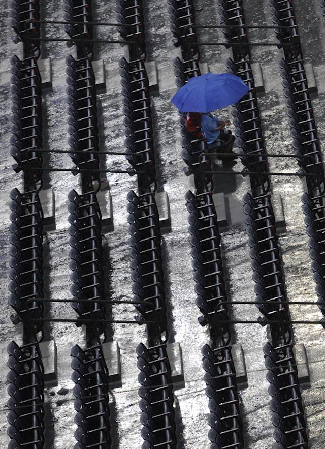 Baseball fans wait for the start of the New York Mets and Atlanta Braves baseball game during a rain delay, Monday, June 17, 2013, in Atlanta. (AP Photo/John Amis)