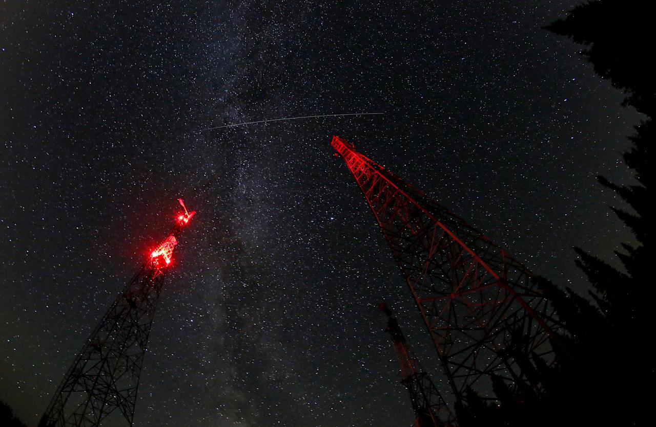 A trace of the Perseid meteor is seen in the moonless night sky over telecommunication masts in the Siberian Taiga area in Krasnoyarsk Region, Russia August 19, 2018. Picture taken with a fish eye lens August 19, 2018. REUTERS/Ilya Naymushin
