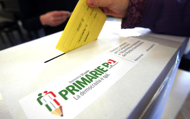 A woman casts her ballot for the Italian Democratic party's primary elections, in Milan - Credit: AP