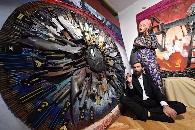 "Ukrainian artists Daria Marchenko and Daniel Green, well known for their portrait of Russian President Vladimir Putin made from bullet shells, speak as they sit in front of their artwork called ""Honour"" in Kiev (AFP Photo/Sergei Supinsky)"