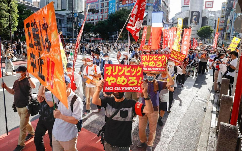 Anti-Olympics protesters march with banners through Shibuya district in Tokyo - Kyodo News via AP