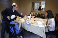 FILE - In this Wednesday, April 8, 2020 file photo, Seth Pollack pours wine for his family, wife Jessica Choe and children Micah and Mina Pollack, as they being their Passover meal in Seattle. With physical distancing guidelines in place because of the coronavirus pandemic, Jewish communities are being forced to scale back or cancel beloved traditions and rituals marking Passover, the holiday celebrating Israelites' freedom from Egyptian bondage and referencing biblical plagues. The week-long festival began Wednesday night with the Seder, a large meal that retells the Exodus story. (AP Photo/Elaine Thompson)