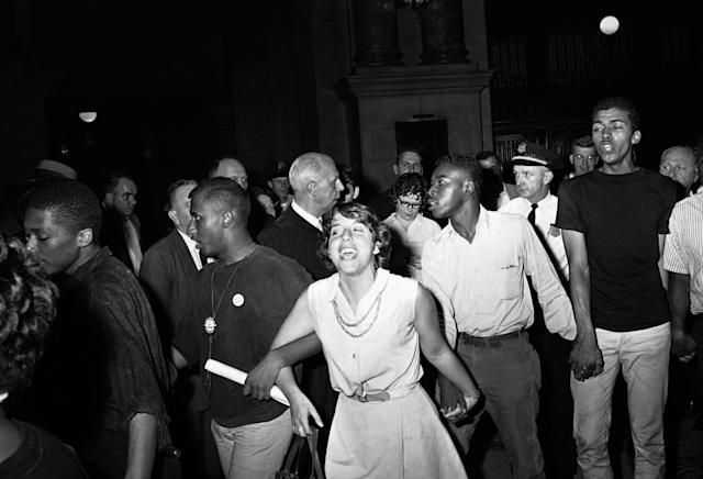 <p>U.S. District Judge William J. Campbell, wearing his robes of office, is flanked by reporters, left, as he orders a group of demonstrators to leave the Federal Building in Chicago on June 25, 1964. At right group, with arms linked and singing, swings past Judge Campbell on way out of building. They had come to ask federal protection for volunteer civil rights workers in Mississippi. (Photo: Charles E. Knoblock/AP) </p>