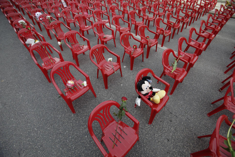 A toys and flowers left on red chairs displayed along main street in Sarajevo to mark the 20th anniversary of the start of the Bosnian War on Friday, April,6, 2012. City officials have lined up 11,541 red chairs arranged in 825 rows along the main street that now looks like a red river. Nobody will be sitting in them since the concert being held is for 11,541 Sarajevans who were killed during the siege.(AP Photo/Amel Emric)