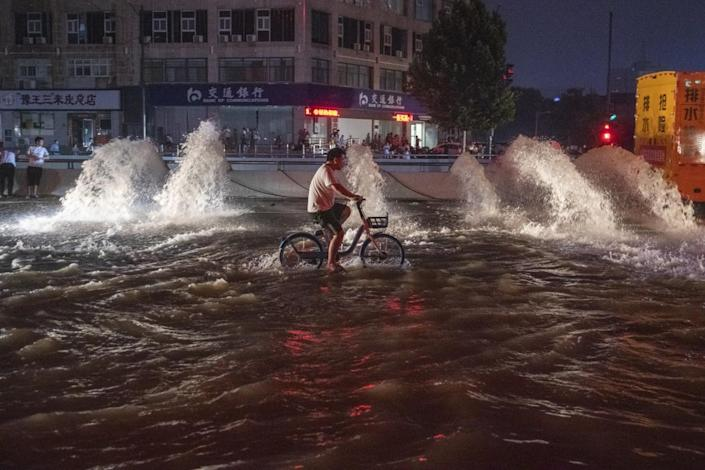 A man rides a bicycle in floodwaters