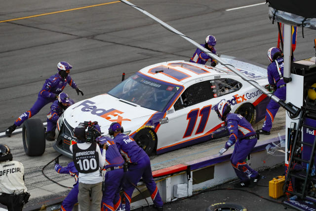 Denny Hamlin's pit crew performs a late pit stop during a NASCAR Cup Series auto race at Pocono Raceway, Sunday, June 28, 2020, in Long Pond, Pa. (AP Photo/Matt Slocum)
