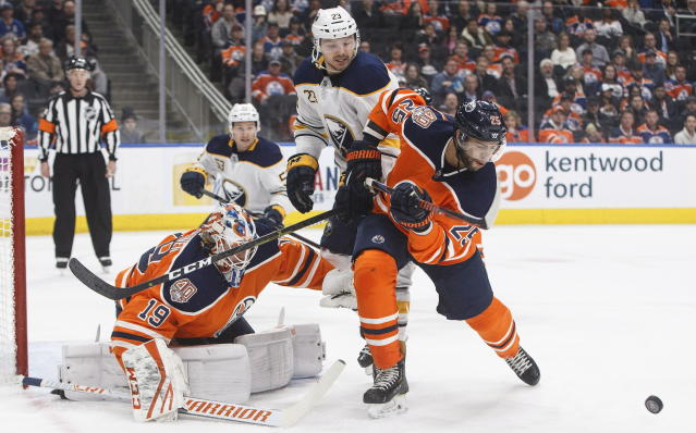 Buffalo Sabres' Sam Reinhart (23) and Edmonton Oilers' Darnell Nurse (25) battle for the rebound as goalie Mikko Koskinen (19) makes the save during first period NHL hockey action in Edmonton, Alberta, on Monday, Jan. 14, 2019. (Jason Franson/The Canadian Press via AP)
