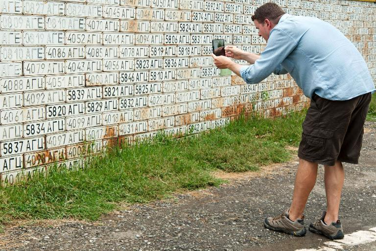 A tourist takes a picture of fence of old car numbers in Vank village in Armenian-controlled Azerbaijani region of Nagorny Karabakh on June 27, 2013