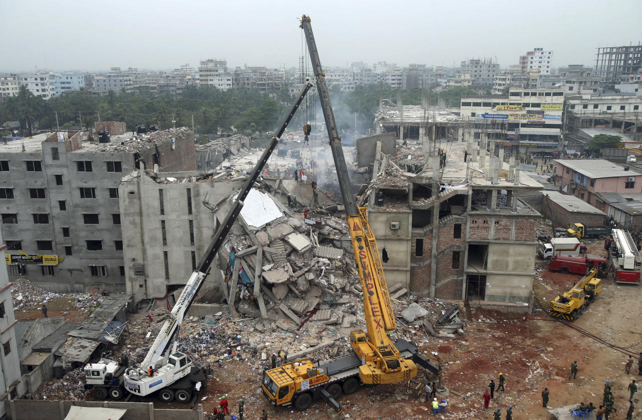 FILE - In this April 29, 2013 file photo, the collapsed Rana Plaza garment factory building is seen from a building nearby as a crane prepares to lift the fallen ceiling in Savar, near Dhaka, Bangladesh. A Bangladeshi garment industry leader on Saturday, April 18, 2015, guardedly welcomed Italian retailer Benetton's pledge of more than $1 million to victims of the factory collapse that killed over 1,100 people two years ago, saying it had come late but was appreciated. (AP Photo/Wong Maye-E, File)