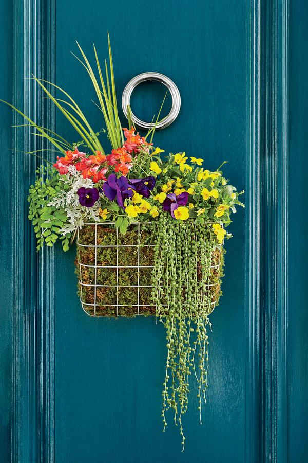 """<p>Forego a traditional round wreath in favor of a modern square basket hung on your <a rel=""""nofollow"""" href=""""http://www.southernliving.com/home-garden/decorating/front-door-colors"""">front door</a>. Line the basket with sheet moss (use empty plastic water bottles to fill space on the inside of the basket, if necessary), fill with soil, and arrange with sprigs of spring flowers and foliage.</p>"""