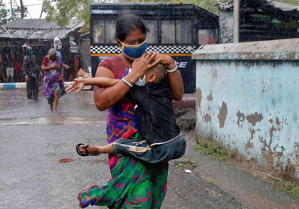 A woman carries her son as she tries to protect him from heavy rain while they rush to a safer place, following their evacuation from a slum area before cyclone Amphan makes its landfall in Kolkata on May 20, 2020. REUTERS/Rupak De Chowdhuri