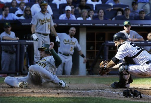 Oakland Athletics' Josh Donaldson, left, scores ahead of the tag by Yankees catcher Russell Martin, right, in the sixth inning of a baseball game at Yankee Stadium in New York, Sunday, Sept. 23, 2012. (AP Photo/Kathy Willens)