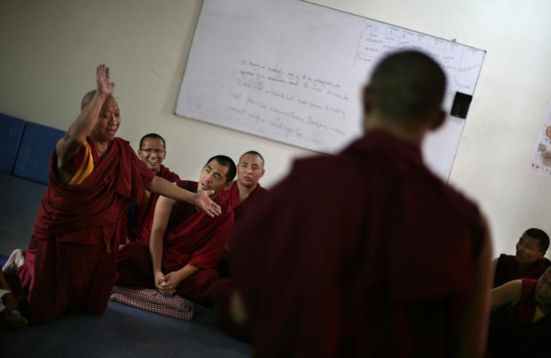 In this June 7, 2012 photo, a Tibetan Buddhist monk smacks his hands during a discussion at an educational complex in Sarah, India. Isolated for centuries atop the high Himalayan plateau, and refusing entry to nearly all outsiders, Tibet long saw little of value in modernity. Education was almost completely limited to monastic schools. Magic and mysticism were - and are - important parts of life to many people. New technologies were something to be feared: Eyeglasses were largely forbidden until well into the twentieth centuries. But not anymore. Pushed by the Dalai Lama, who has became a fierce proponent of modern schooling, a series of programs were created in exile to teach scientific education to monks, the traditional core of Tibetan culture. (AP Photo/Altaf Qadri)
