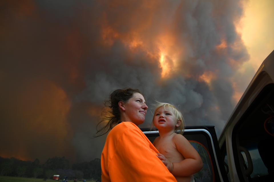 Sharnie Moren and her 18-month-old daughter Charlotte with a backdrop of thick smoke.