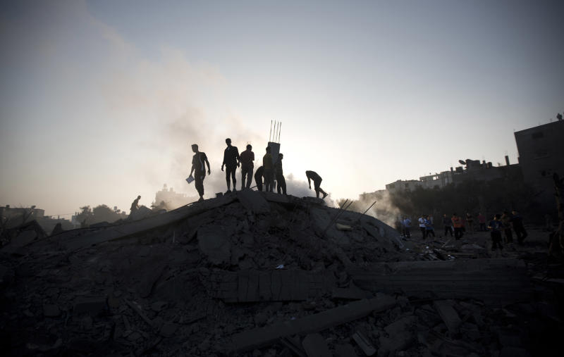Palestinians inspect a damaged building after an Israeli military strike in Gaza City, on July 8, 2014 (AFP Photo/Mahmud Hams)