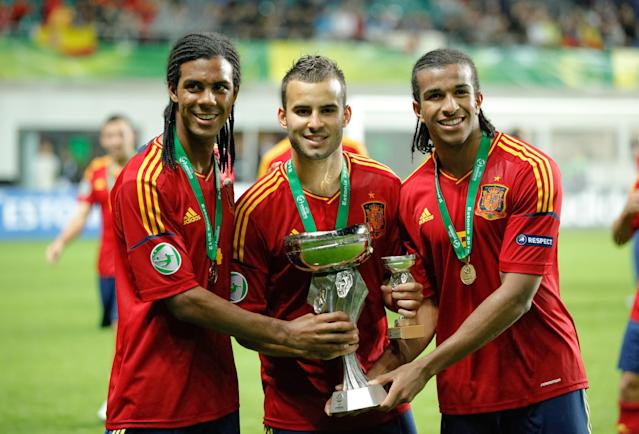 Spanish team players Jonas Ramalho (L), Jese Rodriguez (C), and Derik Osede hold the trophy after their 1-0 victory against Greece in the UEFA European Under-19 football championships final match between Spain and Greece, in Tallin, on July 15, 2012. AFP PHOTO / JAREK JOEPERAJarek Joepera/AFP/GettyImages