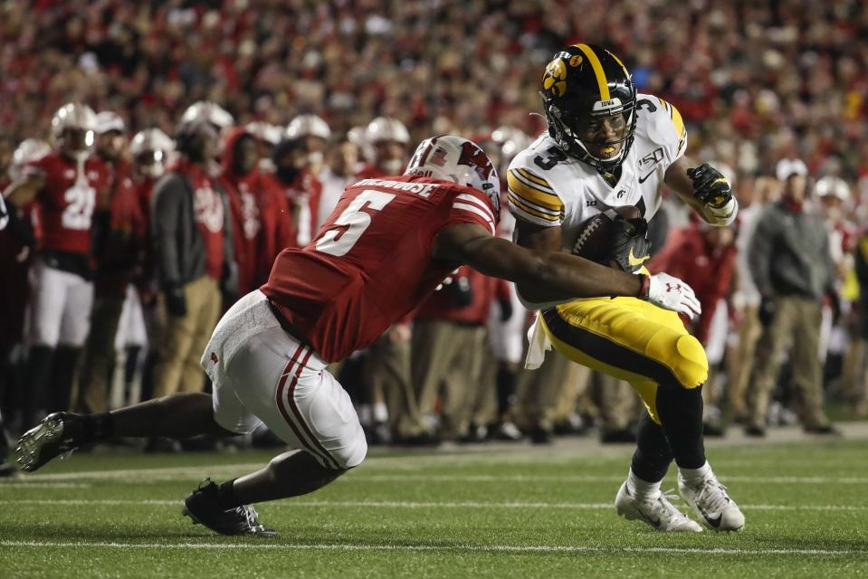 Iowa's Tyrone Tracy Jr. tries to get past Wisconsin's Rachad Wildgoose during the second half of an NCAA college football game Saturday, Nov. 9, 2019, in Madison, Wis. Wisconsin won 24-22. (AP Photo/Morry Gash)