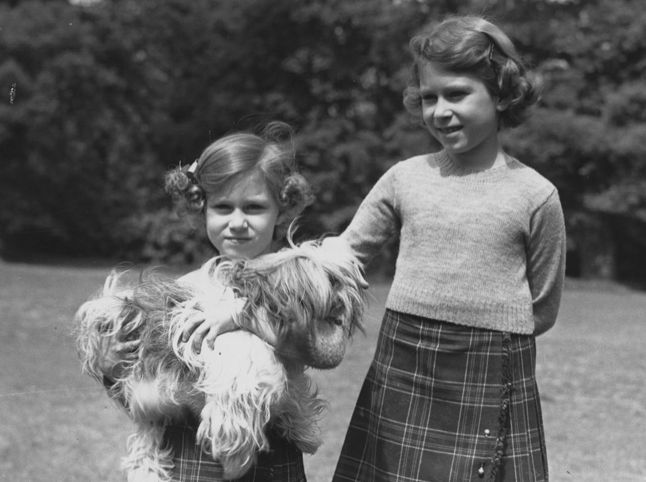 <p>Margaret and Elizabeth on the grounds of Windsor with one of their pet dogs, Chu-Chu.</p>