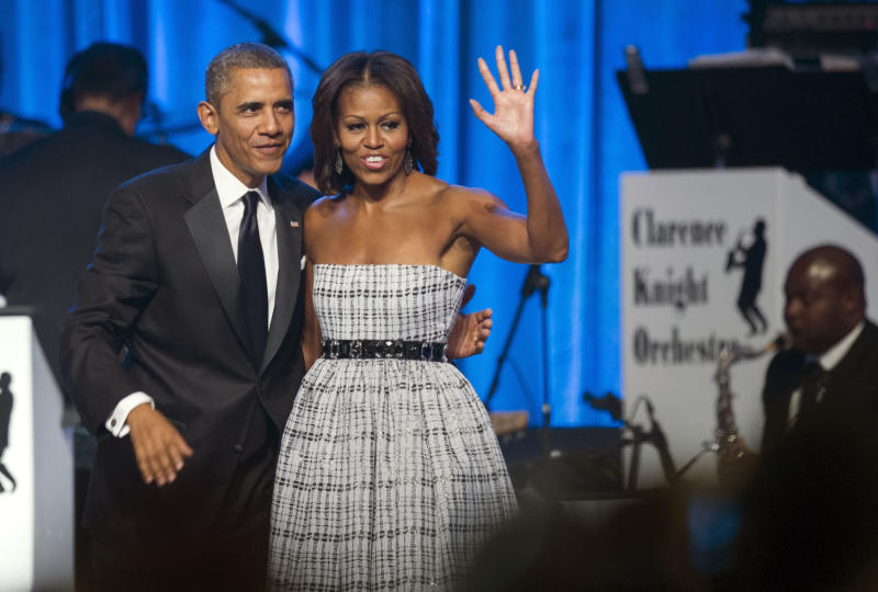 President Barack Obama and first lady Michelle Obama wave as they depart the stage after Obama addressed the 43rd annual Congressional Black Caucus Foundation's Legislative Conference dinner in Washington, Saturday, Sept. 21, 2013. (AP Photo/Cliff Owen)
