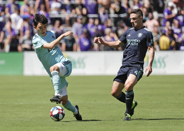 Vancouver Whitecaps' Hwang In-Beom, left, moves the ball past Orlando City's Will Johnson during the first half of an MLS soccer match, Saturday, April 20, 2019, in Orlando, Fla. (AP Photo/John Raoux)