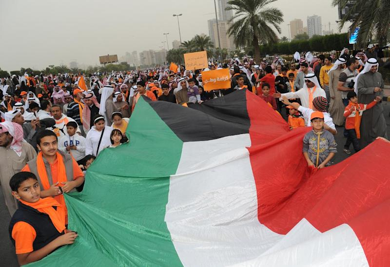 In this Saturday, Dec. 8, 2012 photo, Kuwaiti citizens hold a large national flag as they gather near Kuwait Towers in Bneid Al Ghar, Kuwait, to protest new election rules. Kuwait's ruler has named a new Cabinet that makes no major changes in membership and reinstates the finance minister who resigned earlier this year under pressure from opposition lawmakers.(AP Photo/Gustavo Ferrari)